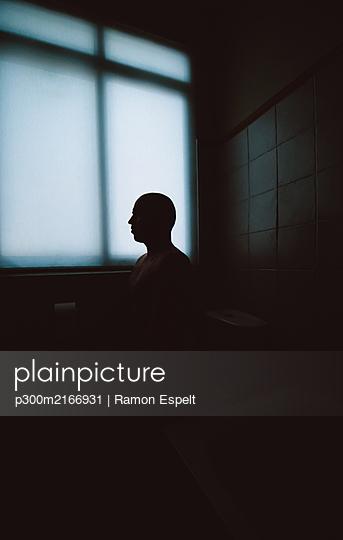 Silhouette of man sitting in bathroom - p300m2166931 by Ramon Espelt