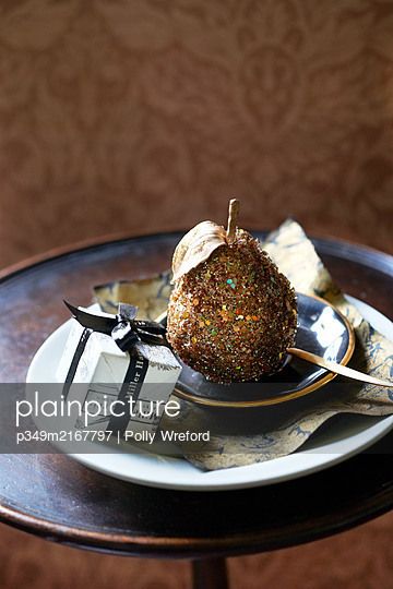 Golden pear and small gift on antique wooden side table - p349m2167797 by Polly Wreford