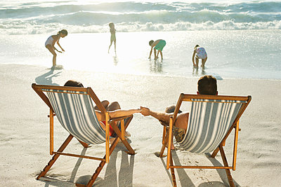 Parents watching children play on beach - p1023m1146343 by Dan Dalton