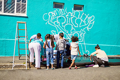 Kid volunteers painting community mural on sunny wall - p1023m2067050 by Trevor Adeline