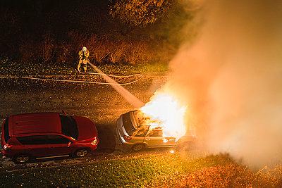 Fireman puts out car fire - p1418m1572142 by Jan Håkan Dahlström