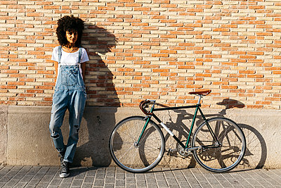 Woman with racing cycle leaning against brick wall - p300m2023650 von Josep Rovirosa
