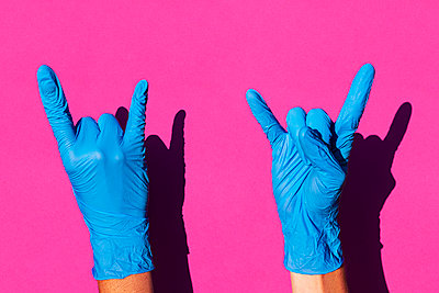 Hands of woman wearing latex gloves making sign of horns - p300m2198289 by Gemma Ferrando