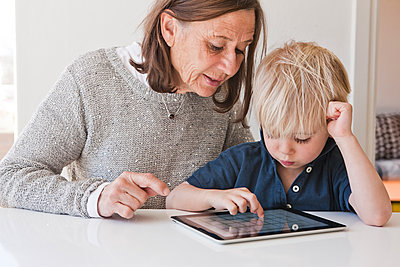 Grandmother with grandson using digital tablet - p312m1075908f by Peter Rutherhagen