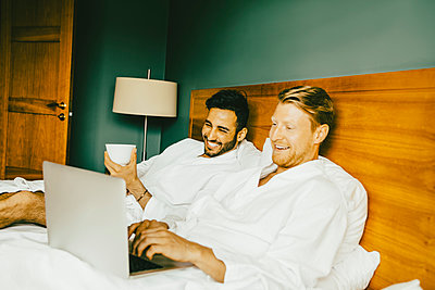 Smiling gay couple using laptop while leaning on bed in hotel room - p426m2127723 by Maskot