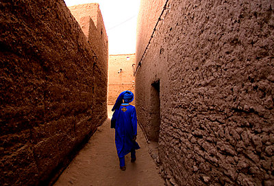Omar walks through his home town, just south of Mahmid, Morocco, North Africa, Africa - p8713625 by James Morgan