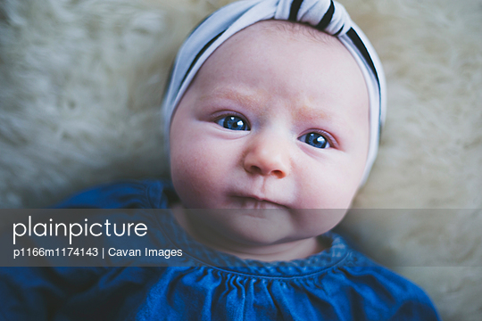 Portrait of baby lying on bed at home - p1166m1174143 by Cavan Images