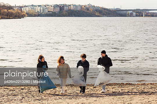 Young male and female environmentalists with collected microplastics walking against lake - p426m2213280 by Maskot