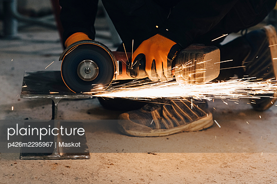 Male worker cutting metal using electric saw while working at construction site - p426m2295967 by Maskot