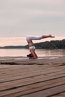 Side view of woman practicing headstand on pier by lake against cloudy sky during sunset - p1166m2011241 by Cavan Images