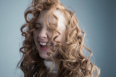 Portrait playful Caucasian woman with messy red curly hair in face - p1192m1213146 by Hero Images