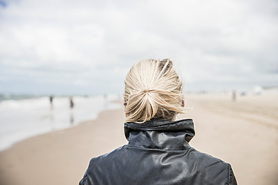 Back view of woman wearing leather jacket on the beach - p300m1175579 by Christophe Papke