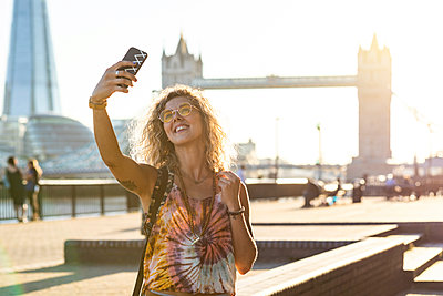 UK, London, smiling young woman taking a selfie with Tower Bridge in background - p300m2062906 by William Perugini
