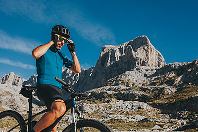 Male cyclist wearing sunglasses at Picos de Europa National Park on sunny day, Cantabria, Spain - p300m2240179 by David Molina Grande