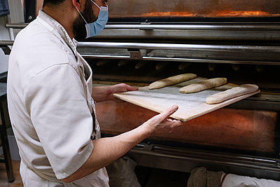 Male chef putting bread dough in oven at bakery during COVID-19 - p300m2243651 by Jose Luis CARRASCOSA