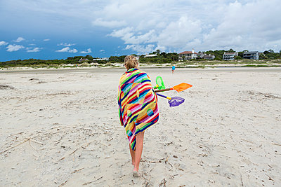 Caucasian girl walking on beach carrying net and shovels - p555m1522726 by Marc Romanelli