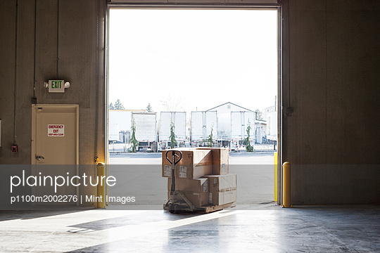 A small stack of products in boxes sitting on a manual pallet jack in a loading dock door at a distribution warehouse. - p1100m2002276 by Mint Images