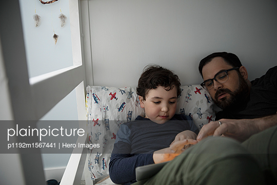 Father and son using digital tablet on bed - p1192m1567441 by Hero Images