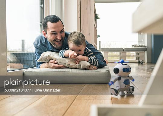 plainpicture - plainpicture p300m2104377 - Excited father and son lyin... - DEEPOL by plainpicture/Uwe Umstätter