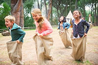 Children having sack race in field - p1023m1146442 by Robert Daly