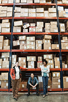 Team portrait of multi-ethnic female warehouse workers in a large distribution warehouse full of products stored on pallets in cardboard boxes on large racks. - p1100m1575502 by Mint Images