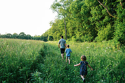 A family walking through a meadow in the evening - p1166m2201268 by Cavan Images