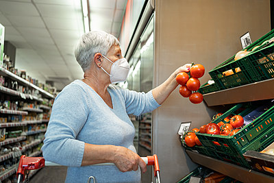 Caucasian elderly woman with white hair  shopping in supermarket - p1166m2208397 by Cavan Images