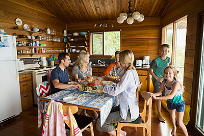 Family around table in cabin - p1192m1078332f by Hero Images