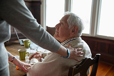 Home caregiver comforting senior man at table - p1192m1583457 by Hero Images