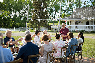 Senior man giving celebratory toast at garden party table - p1192m2009289 by Hero Images