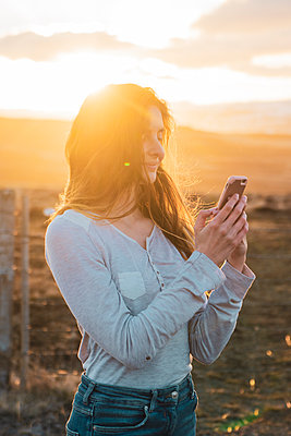 Iceland, woman using smartphone at sunset - p300m2005543 von Kike Arnaiz