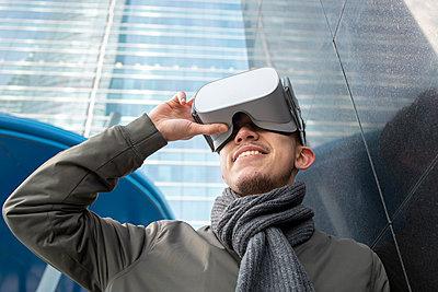 Smiling young man wearing virtual reality simulator by black wall - p300m2242643 by Ignacio Ferrándiz Roig