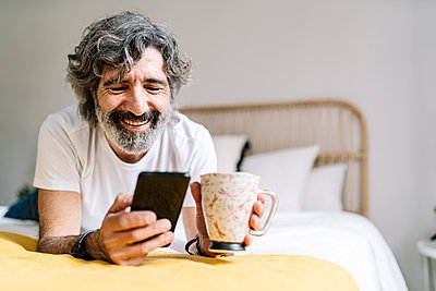 Happy senior man using smart phone holding coffee mug while lying on bed at home - p300m2277166 by COROIMAGE