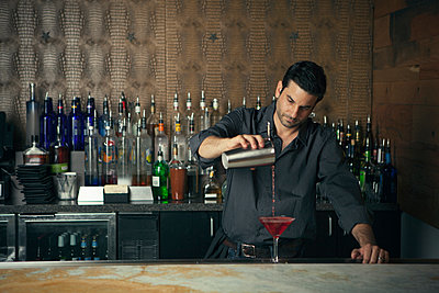 Caucasian bartender pouring drinks at bar - p555m1415309 by King Lawrence