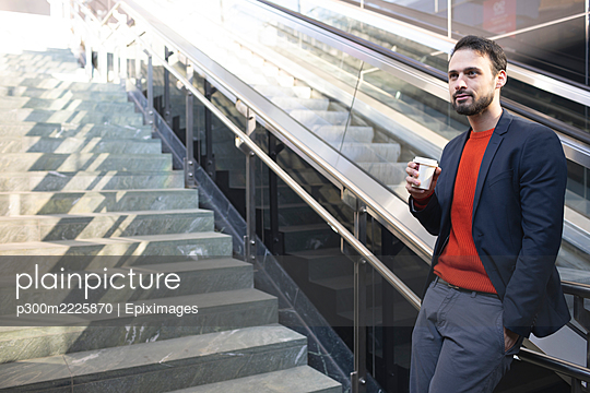 Confident businessman drinking coffee while standing on staircase in city - p300m2225870 by Epiximages