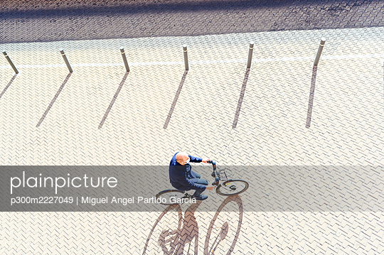 Man cycling on footpath during coronavirus - p300m2227049 by Miguel Angel Partido Garcia