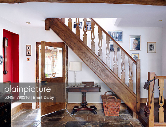 Family photographs hang on staircase with wooden banister in flagstone entrance foyer