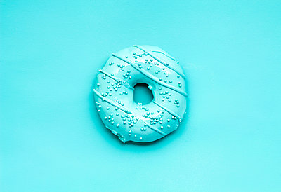 Overhead view of donut over blue background - p1166m1561500 by Cavan Images
