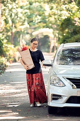 A woman hold a paper bag of dry flower and back to car after shopping - p1166m2234746 by Cavan Images