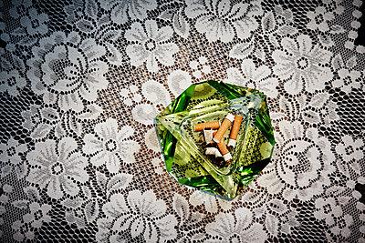 Aschenbecher auf Tischdecke - p415m1149748 von Tanja Luther