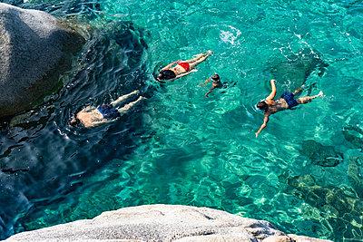Family of four swimming in crystal clear sea, Cagliari, Sardinia - p429m2152960 by Roberto Peri