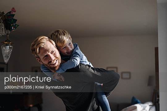 Happy father carrying son piggyback at home - p300m2167235 by Kniel Synnatzschke