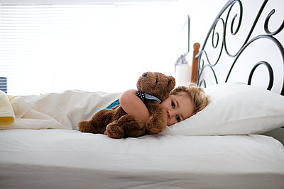 little girl laying in bed snuggling teddy bear looking at camera - p1166m2159366 by Cavan Images
