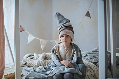 Boy with blanket sitting on the bed  - p1414m1592118 by Dasha Pears