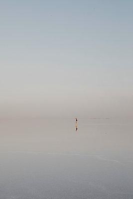 Distant view of woman standing at Lake Karum, Danakil Depression, Ethiopia, Afar - p300m2198532 by letizia haessig photography