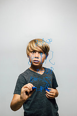 Boy holding blue marker pen staring at equation on glass wall - p429m1504961 by JFCreatives