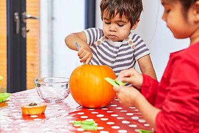 Boy gutting pumpkin in kitchen - p429m2091677 by Sverre Haugland