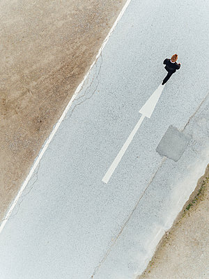 Man walking on country road with directional arrow, aerial view - p586m1088328 by Kniel Synnatzschke