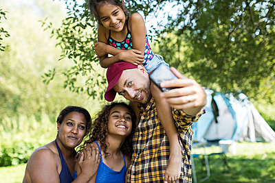 Happy, affectionate family taking selfie with camera phone at campsite - p1023m2066728 by Sam Edwards