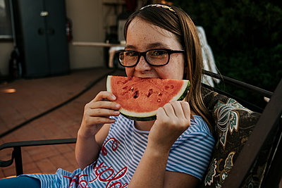 Portrait of girl wearing eyeglasses eating watermelon while sitting on chair in yard - p1166m2067638 by Cavan Images